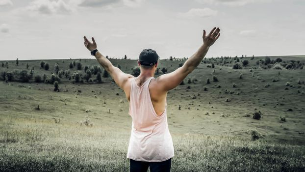 A man in nature with his arms outstretched to the sides,a man demonstrates freedom,a young man is happy in nature in a field in a meadow.