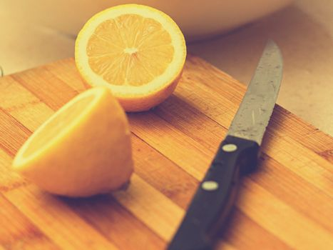 Two limes sitting on top of a wooden cutting board