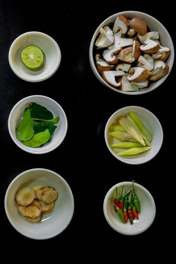 Chili peppers with lime, mint, mushrooms, cucumber, walnut bowl with black background
