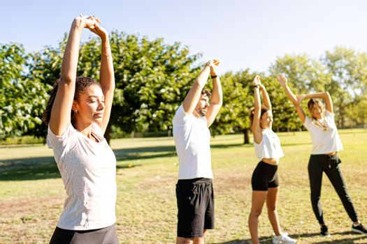Beautiful young curly hispanic woman teach training with closed eyes together with her three friends in the nature - Cute latina athletics instructor stretching her arms with closed eyes in the park