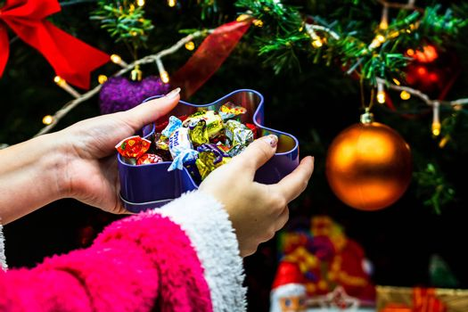 Hands holding box with candies in front of Christmas tree. Unpacking Christmas gifts isolated.