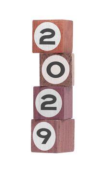 Four isolated hardwood toy blocks, saying 2029