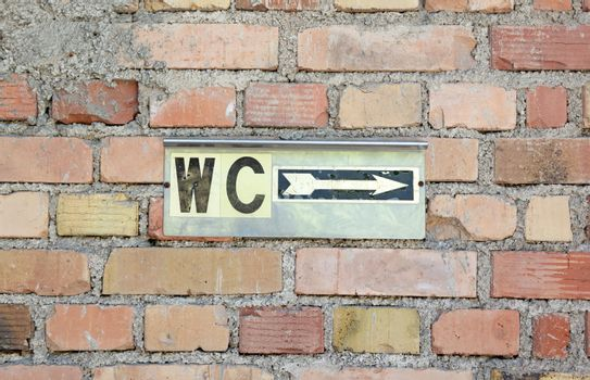 Toilet sign on an old brick wall