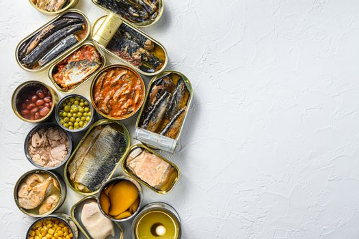 Different canned conserve products in tin cans. Saury, mackerel, sprats, sardines, pilchard, squid, tuna pinapple, corn, peas, mango , beans, over white textured background top view space for text