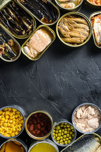 Canned conserve products in tin cans. with fresh organic ingridients Saury, mackerel, sprats, sardines, pilchard, squid, tuna pinapple, corn, peas, mango , beans, over black stone textured background top view copyspace side by side vertical center text concept