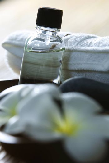 massage oil and towel on the bamboo background