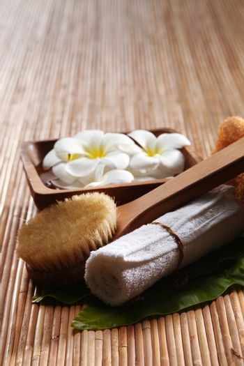 brush, towel and white frangipani on bamboo mat