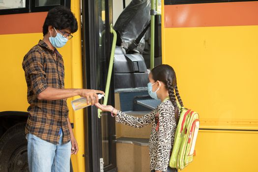 Teacher Providing hand sanitizer to students before going or getting inside the school bus while maintaining social distance as coronavirus or covid-19 safety measures
