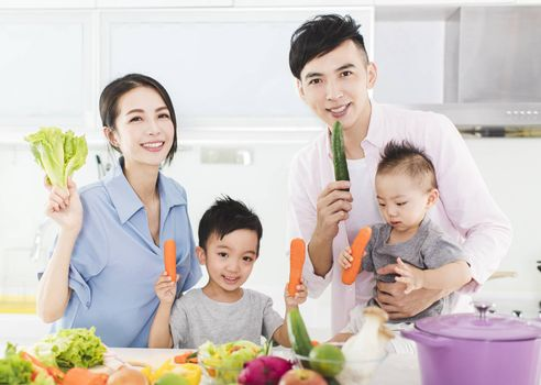 happy family showing healthy  food in kitchen