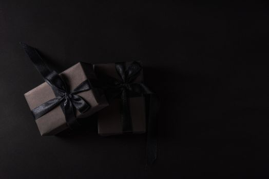 Black Friday sale shopping concept, Top view of gift box wrapped in black paper and black bow ribbon, studio shot on black background
