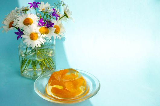 Breakfast jelly with tangerine slices and a bunch of daisies on a blue background.