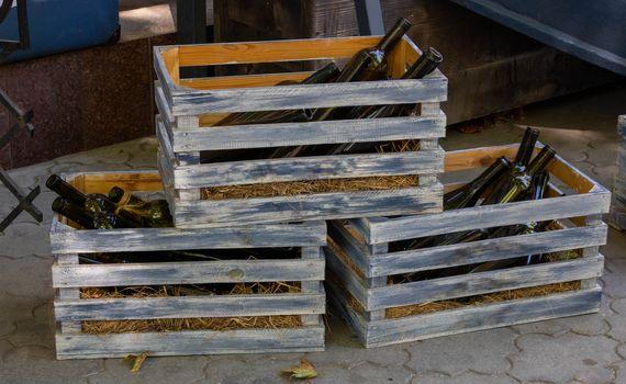 Empty wine bottles in gray wooden crates.