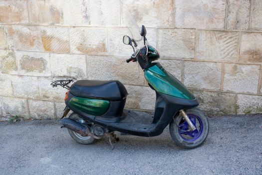 A green scooter is parked in an alley near a stone wall. Fast delivery
