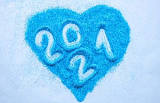 Heart of blue sequins. Numbers 2021 on blue sequins in the shape of a heart.Happy new year 2021.New year's concept
