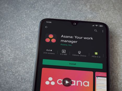 Lod, Israel - July 8, 2020: Asana app play store page on the display of a black mobile smartphone on ceramic stone background. Top view flat lay with copy space.