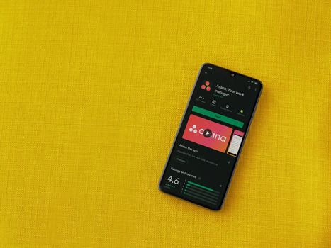 Lod, Israel - July 8, 2020: Asana app play store page on the display of a black mobile smartphone on a yellow fabric background. Top view flat lay with copy space.