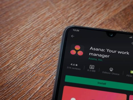 Lod, Israel - July 8, 2020: Asana app play store page on the display of a black mobile smartphone on wooden background. Top view flat lay with copy space.