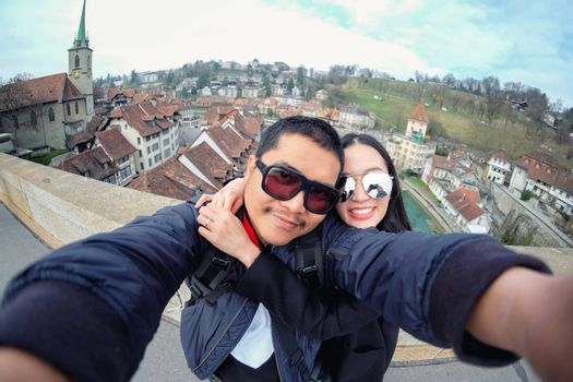 Young Couple Tourists selfie with mobile phone near old town in Bern at Switzerland