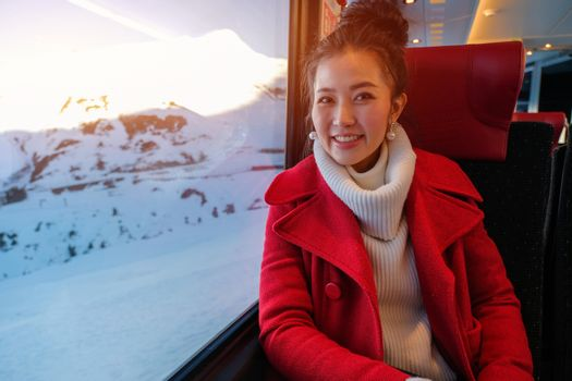 Young woman traveling looking view while sitting in the train.