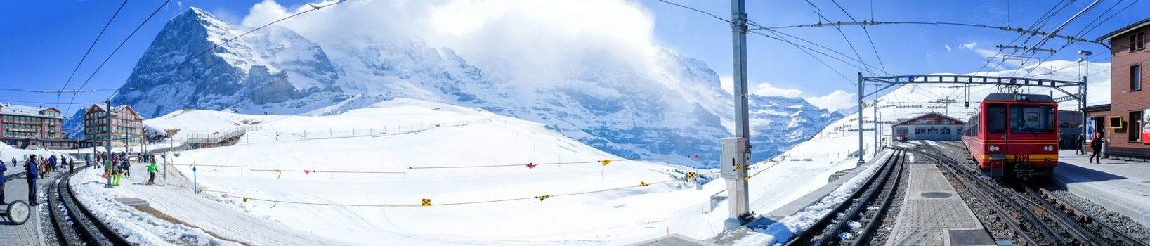 KLEINE SCHEIDEGG, SWITZERLAND - MARCH 28: Panoramic view Tourist train is coming down from the Jungfrau in Kleine Scheidegg, Switzerland on March 28 2017. It's a mountain pass at an elevation of 2,061m.