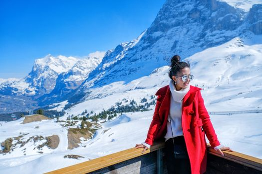 Young Woman Tourists see beautiful viewpoitn near Kleine Scheidegg station, along the railway from Interlaken to Jungfraujoch (3,466 m). In daylight atI Switzerland