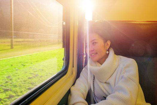 Young beautiful woman traveling looking view while sitting in the train.