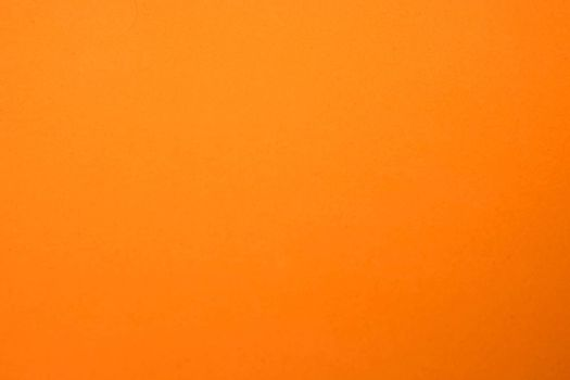 Light orange matte background of suede fabric, closeup. Velvet texture of seamless ginger woolen felt