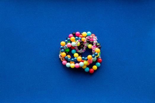 Eight multi-colored bracelets arranged in a flower shape on a blue background. Bracelet with beads.