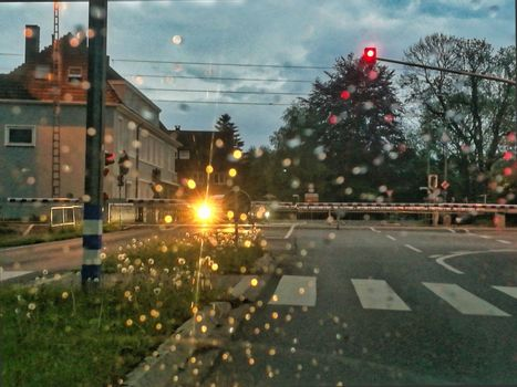 Closed barriers of a railroadcrossing at dusk in the rain
