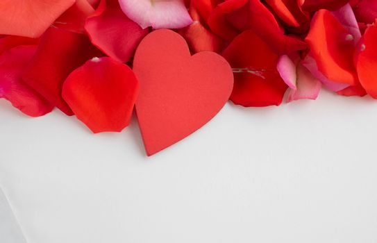 On the red rose petals is a red wooden heart.Concept of mother's Day, family Day, Valentine's Day, March 8