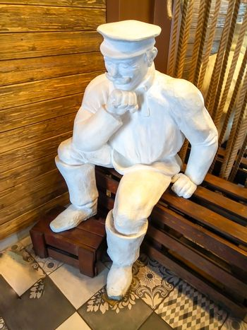 A white statue of a tired Miller sitting on a bench. Travel around the country