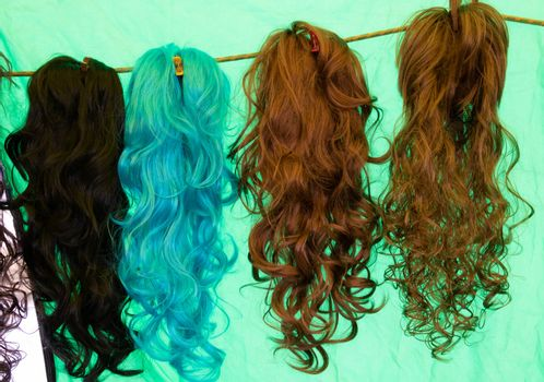 Coloured wigs with long wavy fake hair hanging next to each other