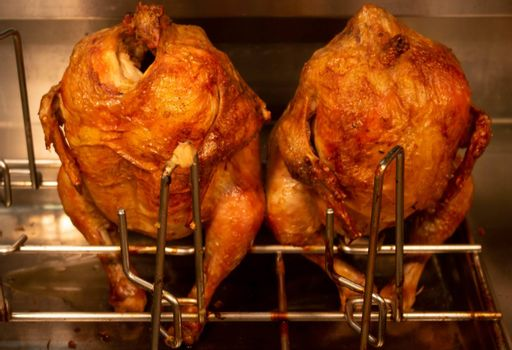 two carcasses of grilled chickens sit behind the glass of the window. market