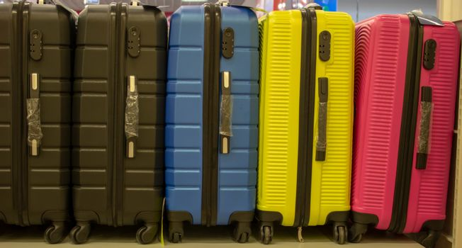 Colourful suitcases put in front of the shop. Suitcases that people on vacation often buy. Ready-to-sell suitcases in front of the store