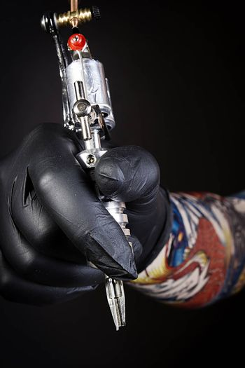 Tattoo machine in artist's hand isolated on black background