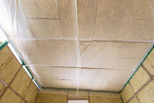 Insulated ceiling of a country house, insulation is closed with a vapor barrier film