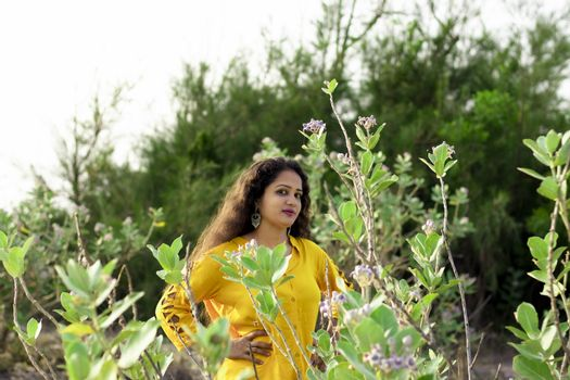 A beautiful Asian woman is standing near the Aak, Madar (Calotropis gigantea) tree wearing a yellow top and selective focus points background,outdoors portrait