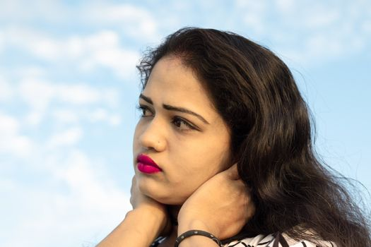 Close up photo shot of an Indian model with beautiful face with blurred background of sky with white clouds and looking away
