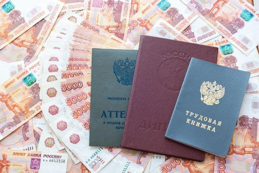 A certificate, a red diploma and a work book are on the five thousandth Russian rubles