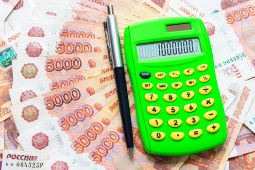 A calculator with the number one million and a ballpoint pen lie against the background of Russian five-thousandth bills