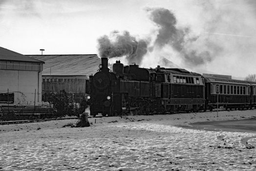 A black and white picture of a steam engine in Austria as it passes some buildings and the ground covered in snow.