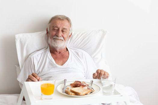 Senior retirement male has breakfast with orange juice and water on bed