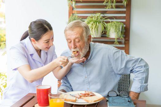 Nurse assist senior man having breakfast together