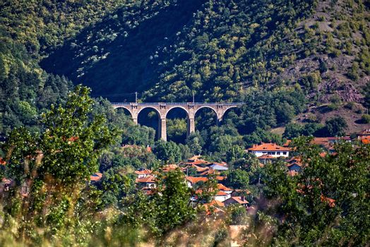 Old railway viaduct in the mountains. Train bridge landscape.