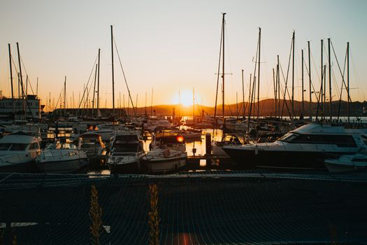 Docks on spain during a burning sunset with a lot of yachts