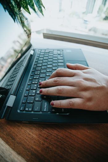 A female hand working on a black laptop over a wooden table during a bright day
