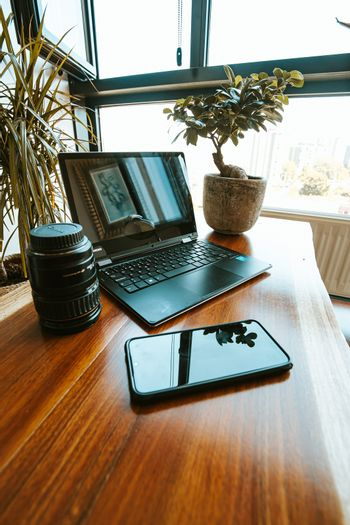 A work space composition with a black mobile phone, a plant, a photography lens and a black laptop
