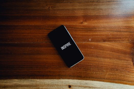 A flat lay of a black phone over a wood background with the word inspire written in it