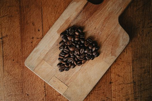 A flat lay of a heart symbol made of coffee grains over two wood tables