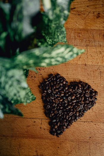 A flat lay of a heart symbol made of coffee grains over a wood table with some leaves decorating